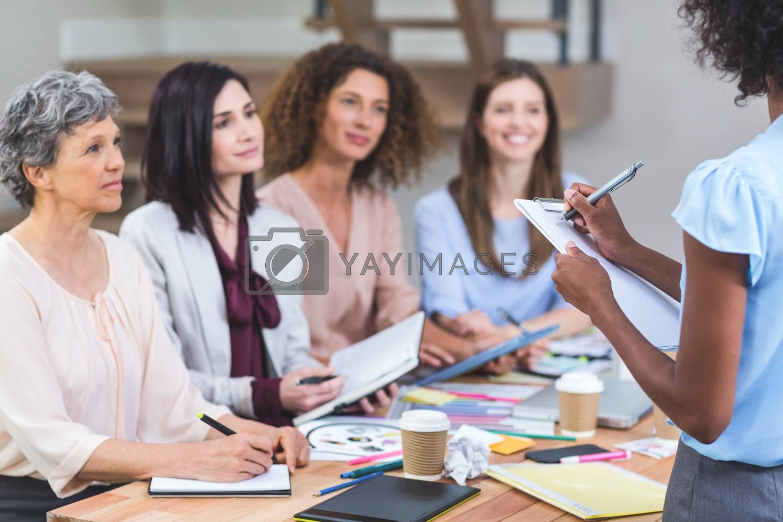 Woman noting on clipboard while colleagues listening presentation in office