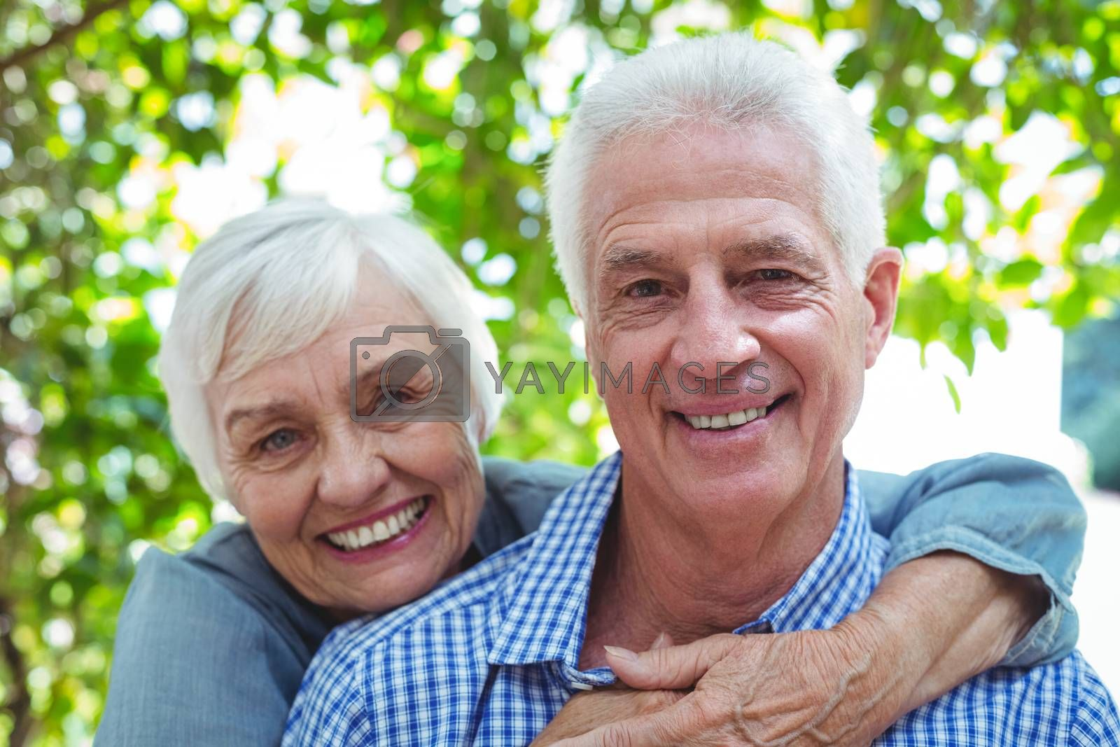 Portrait of confident retired couple embracing