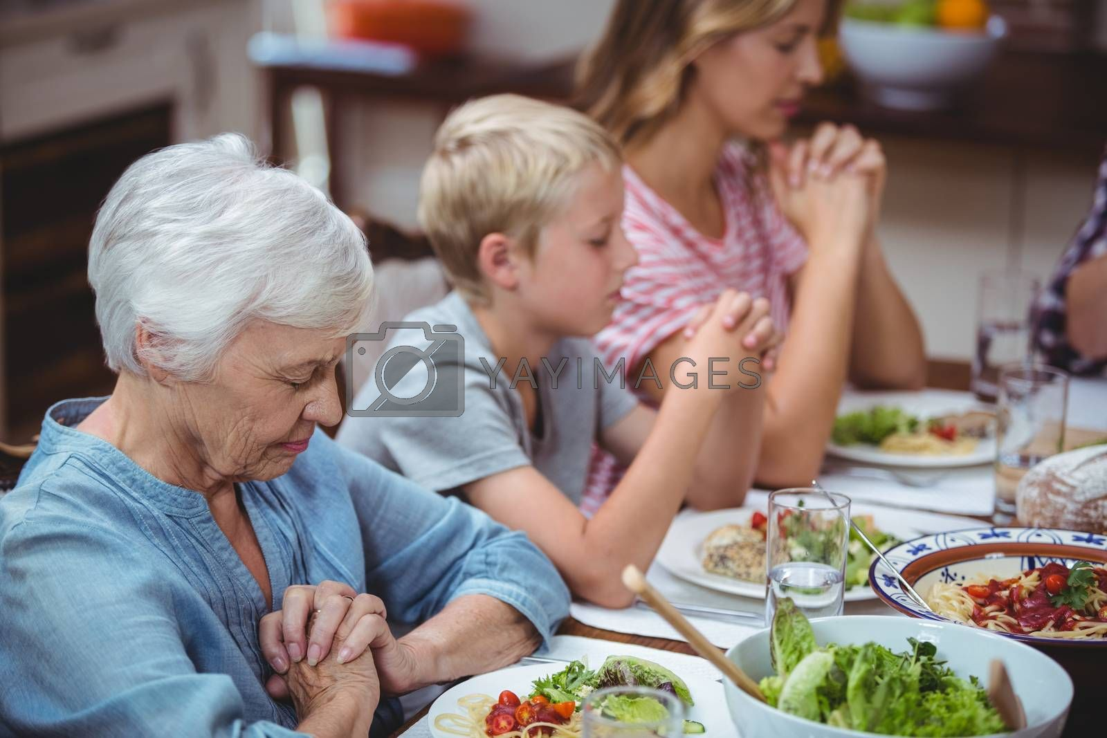 Multi generation family praying with granny sitting at dining table in home