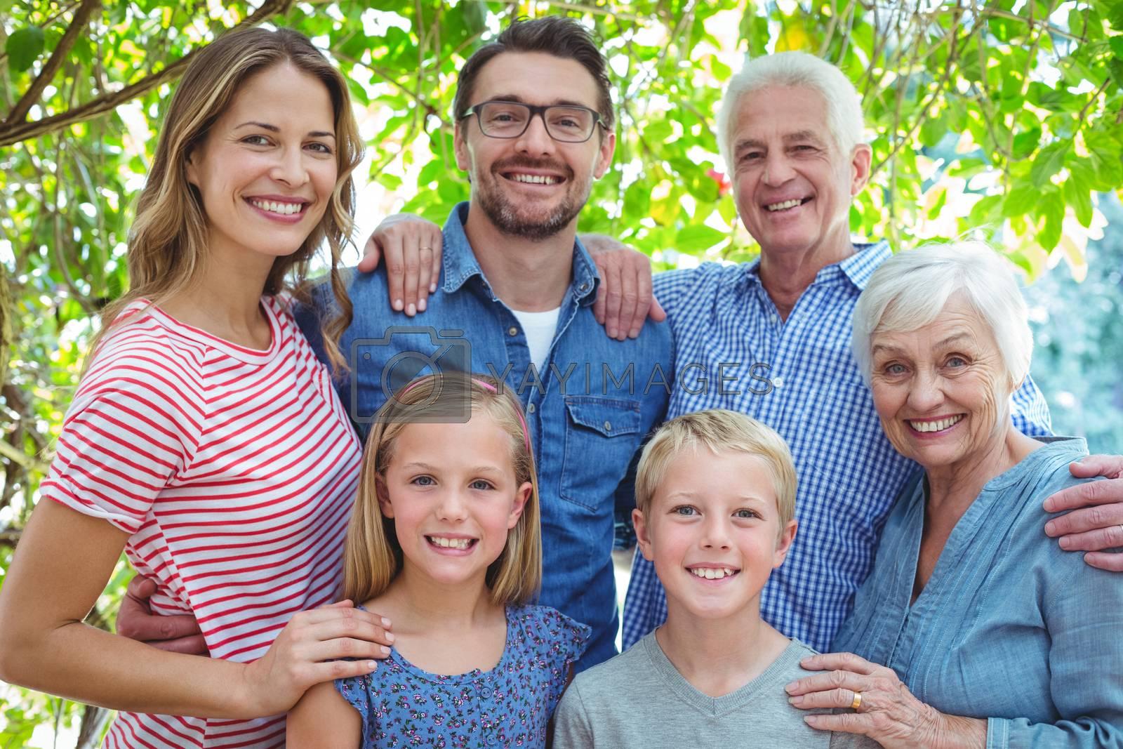 Portrait of smiling family standing against tree