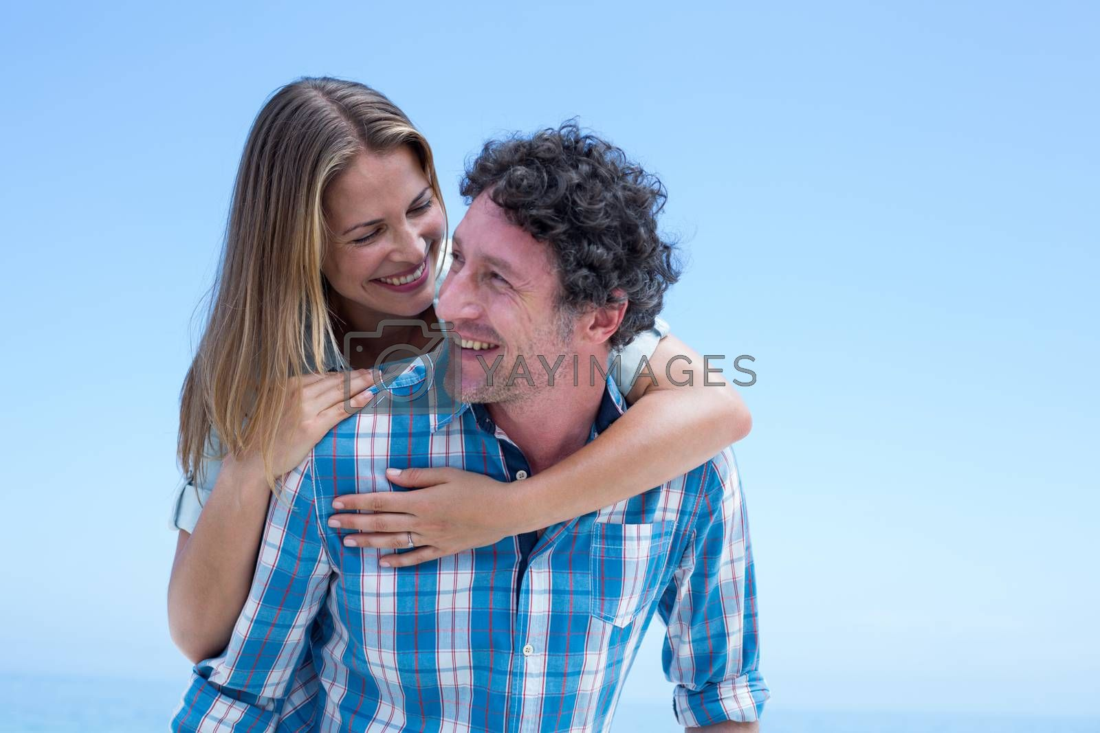 Happy man carrying woman on back against clear blue sky at beach