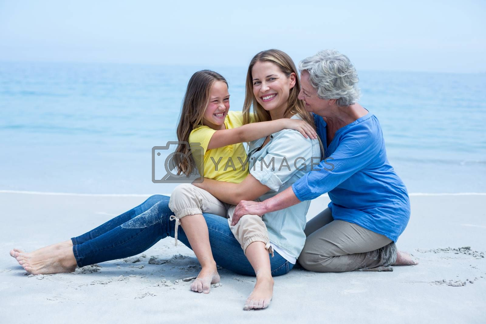 Cheerful multi-generation family resting at sea shore