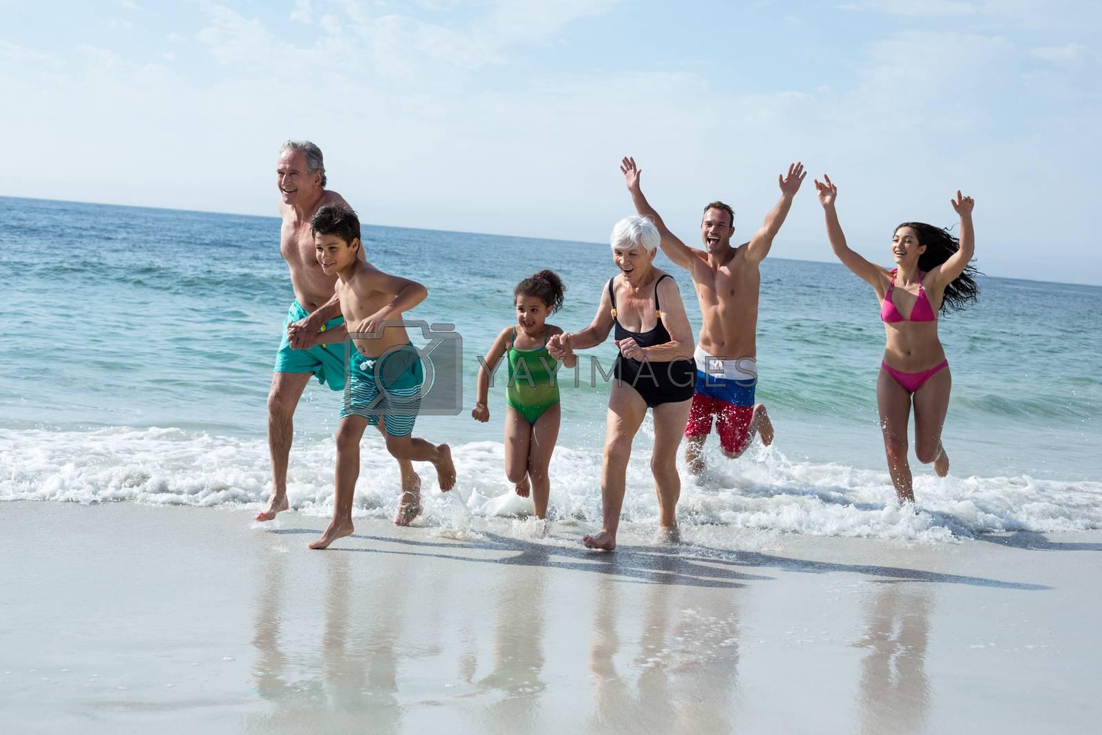 Multi-generation family running on sea shore at beach