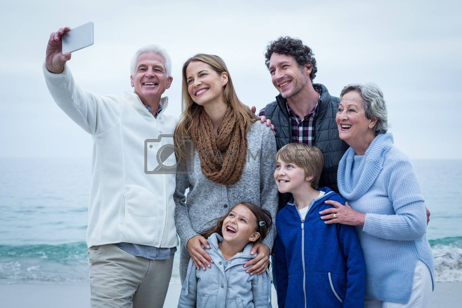 Grandfather taking selfie with cheerful family at sea shore against sky
