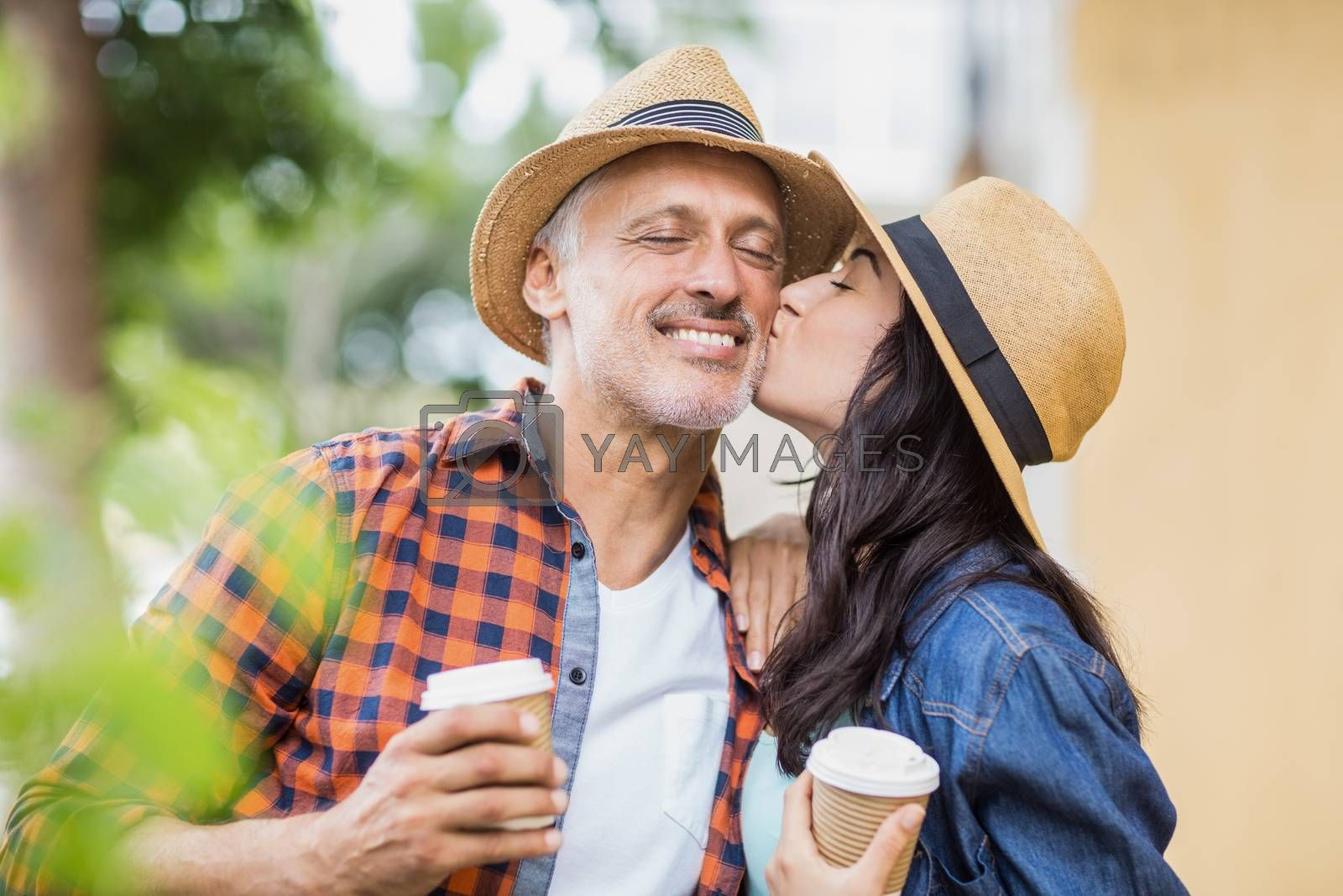 Woman kissing on man's cheek while holding coffee cup