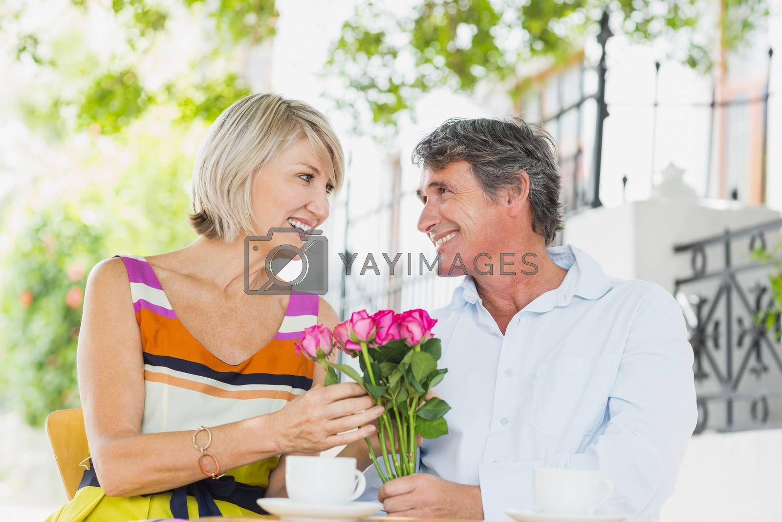 Happy couple sitting with flower bouquet at cafe
