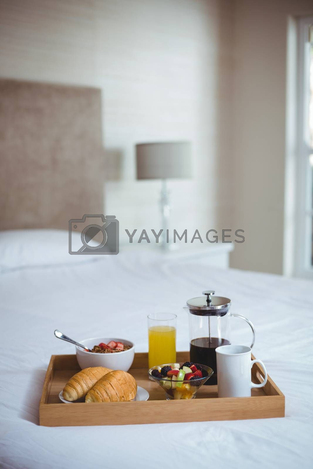 Various food and drink in serving tray on bed