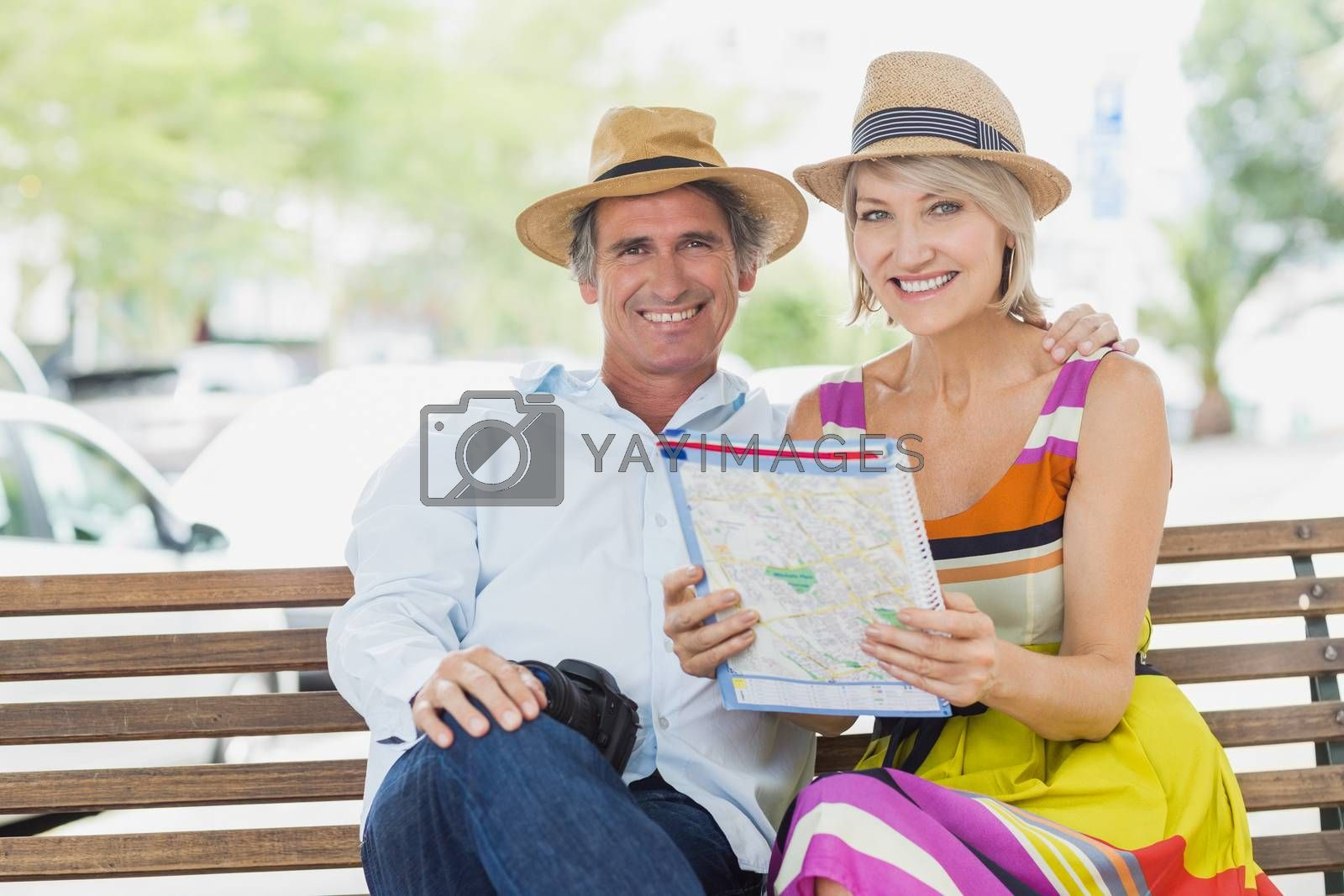 Portrait of happy couple sitting with map in park