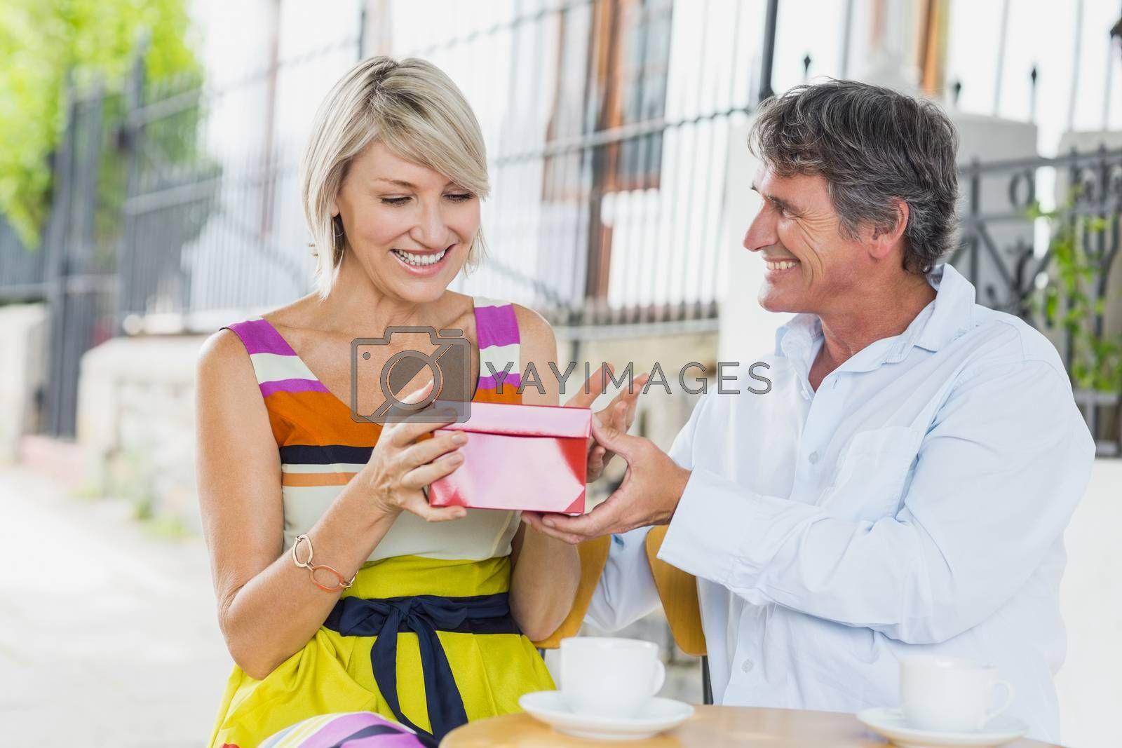 Woman receiving gift from man while sitting at cafe