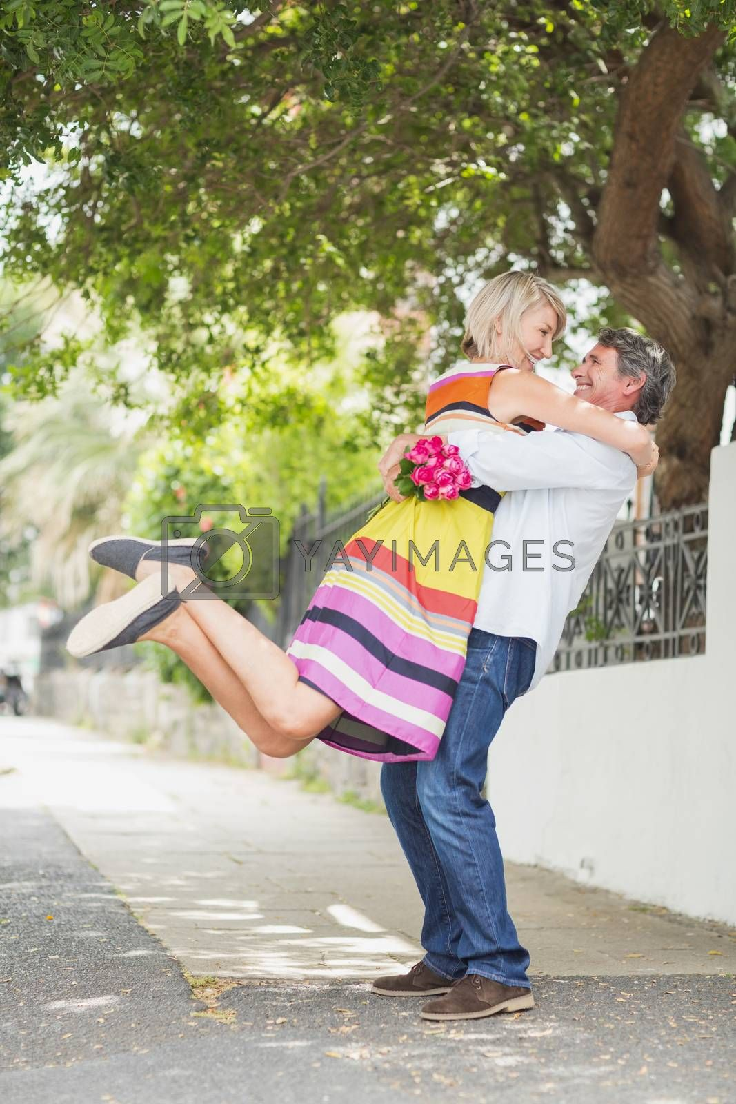 Side view of man lifting woman with flower bouquet on sidewalk in city