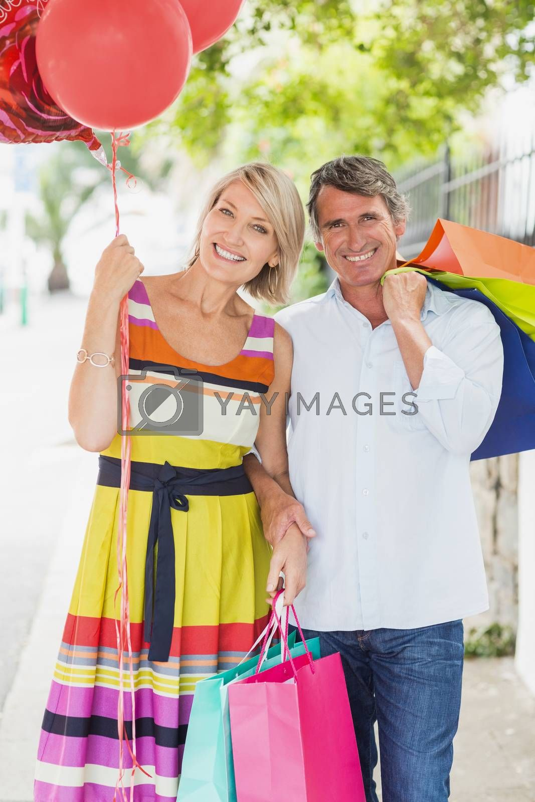 Portrait of couple with shopping bags and balloons in city