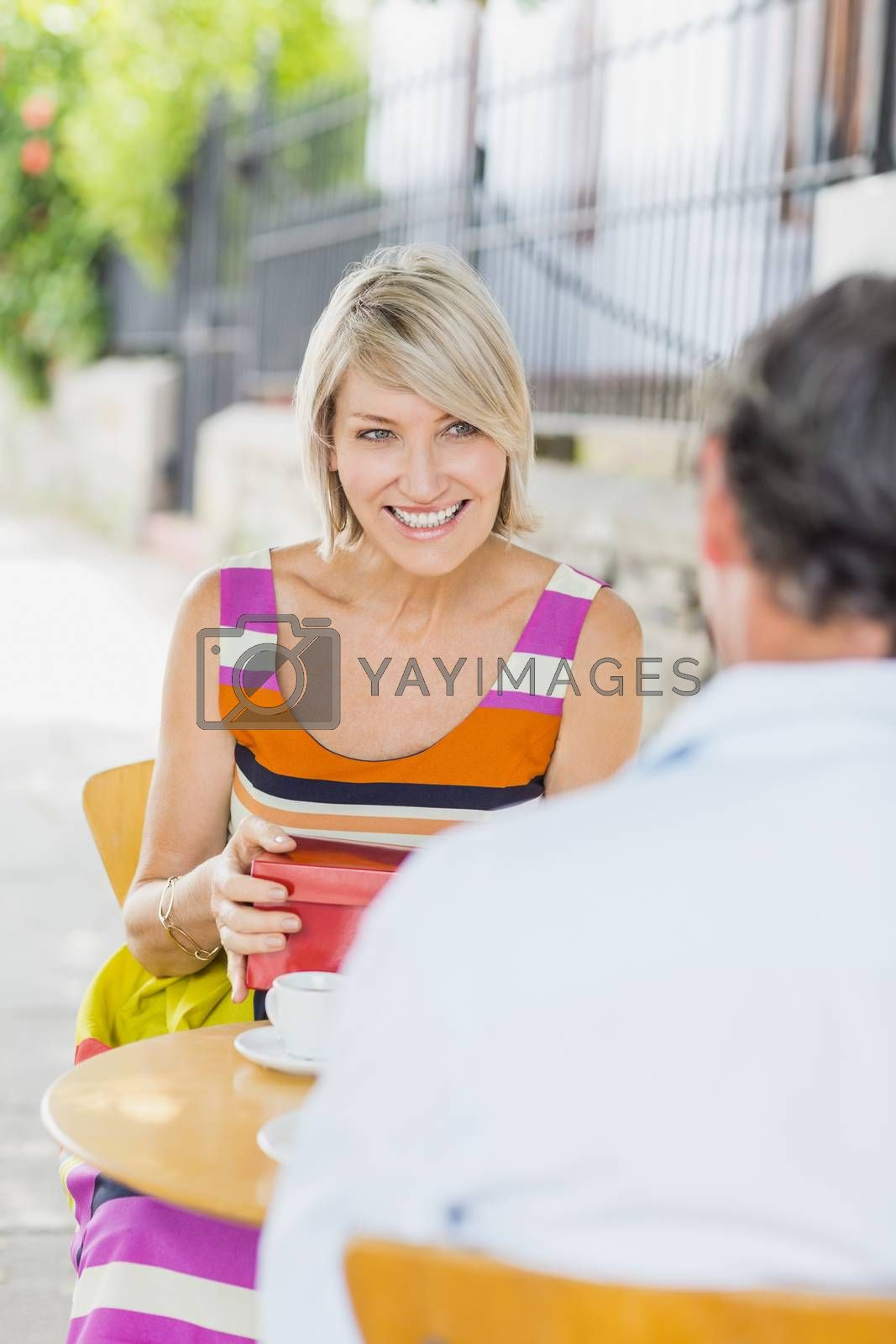 Woman with gift looking at man while sitting in cafe