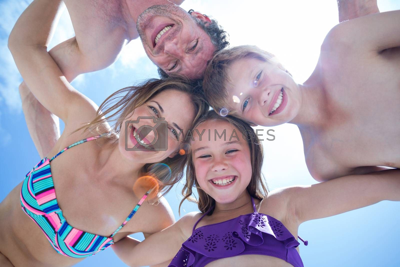 Directly below shot of happy family huddling against sky