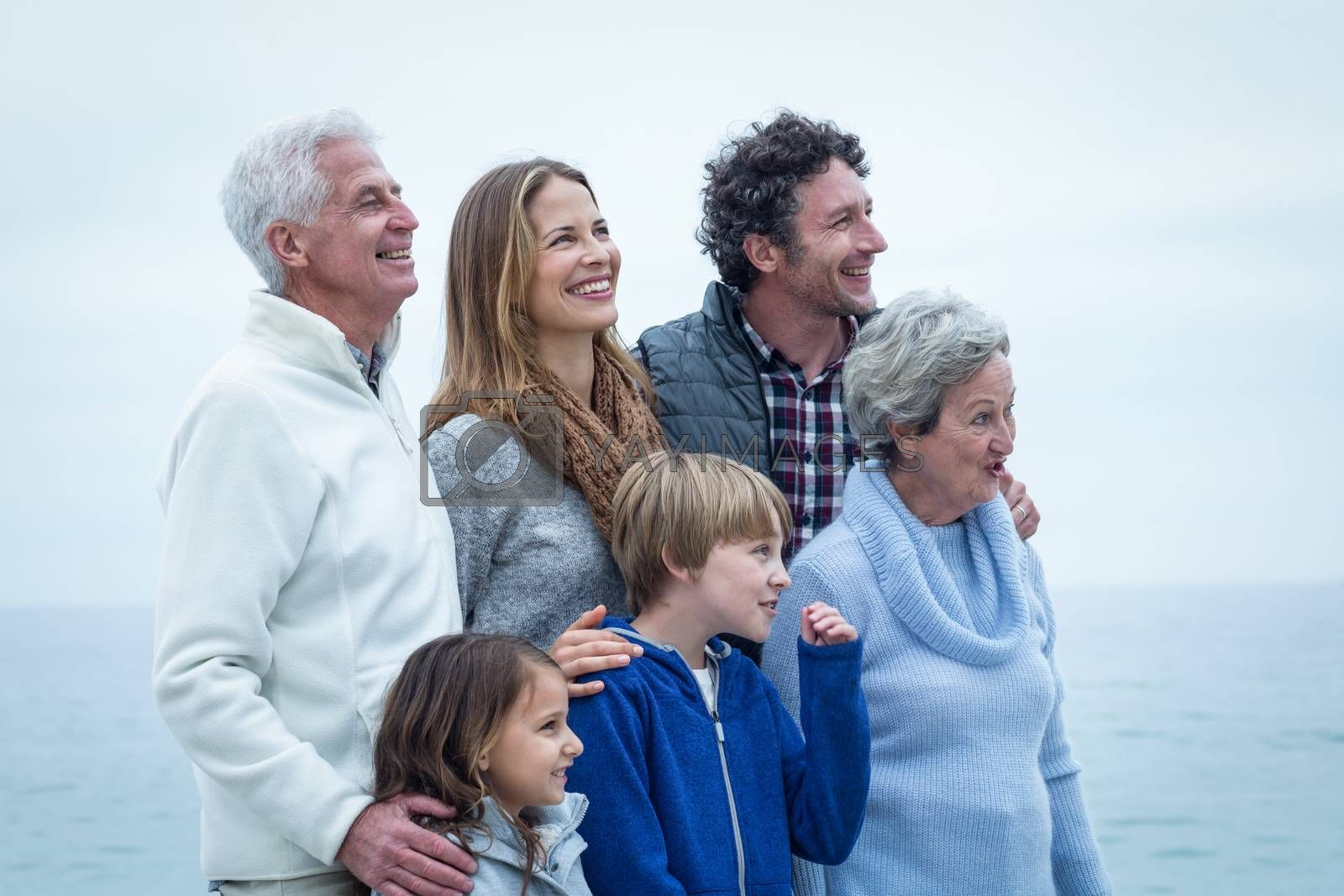 Cheerful family looking away at beach against sky