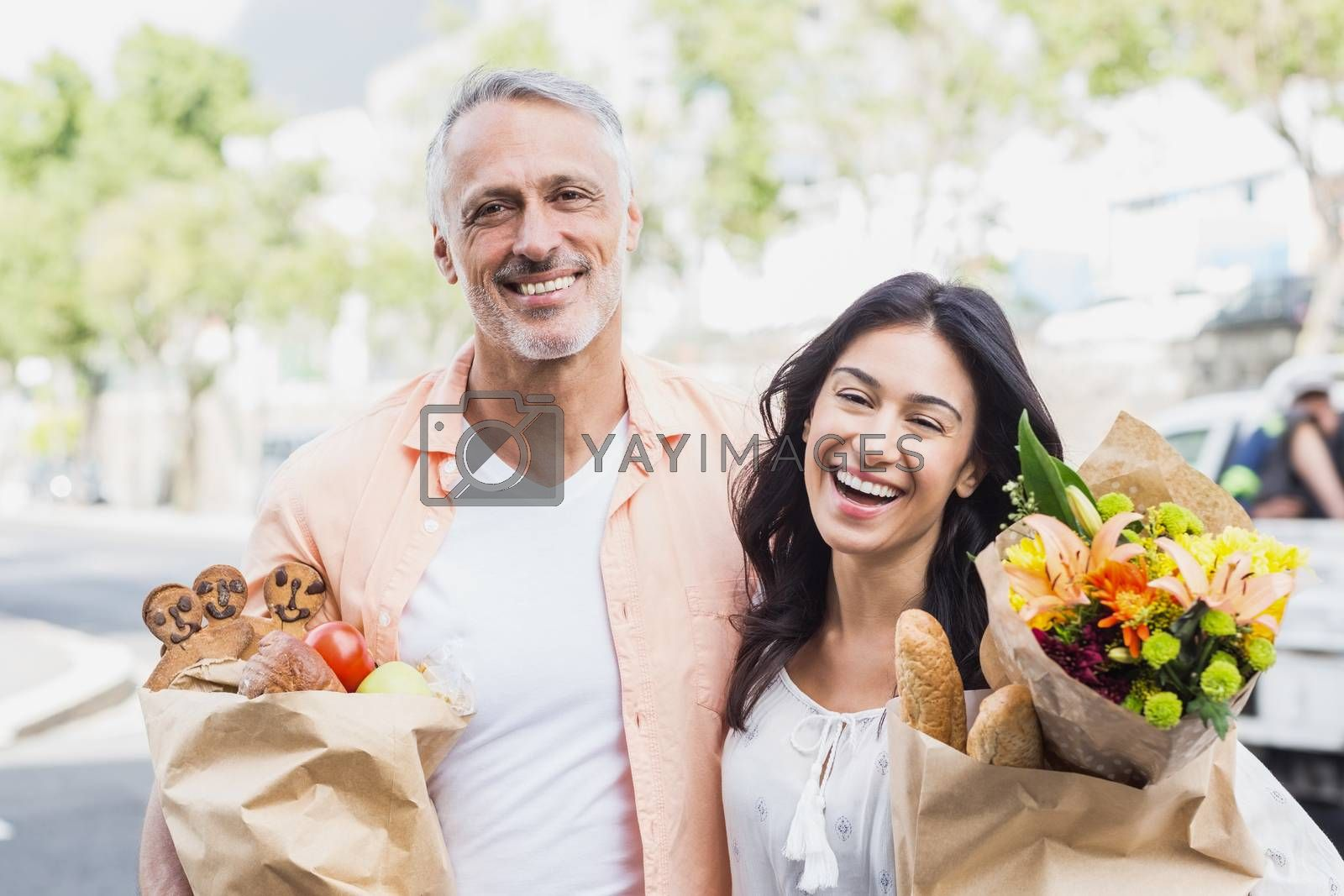 Portrait of happy couple with grocery bags standing outdoors