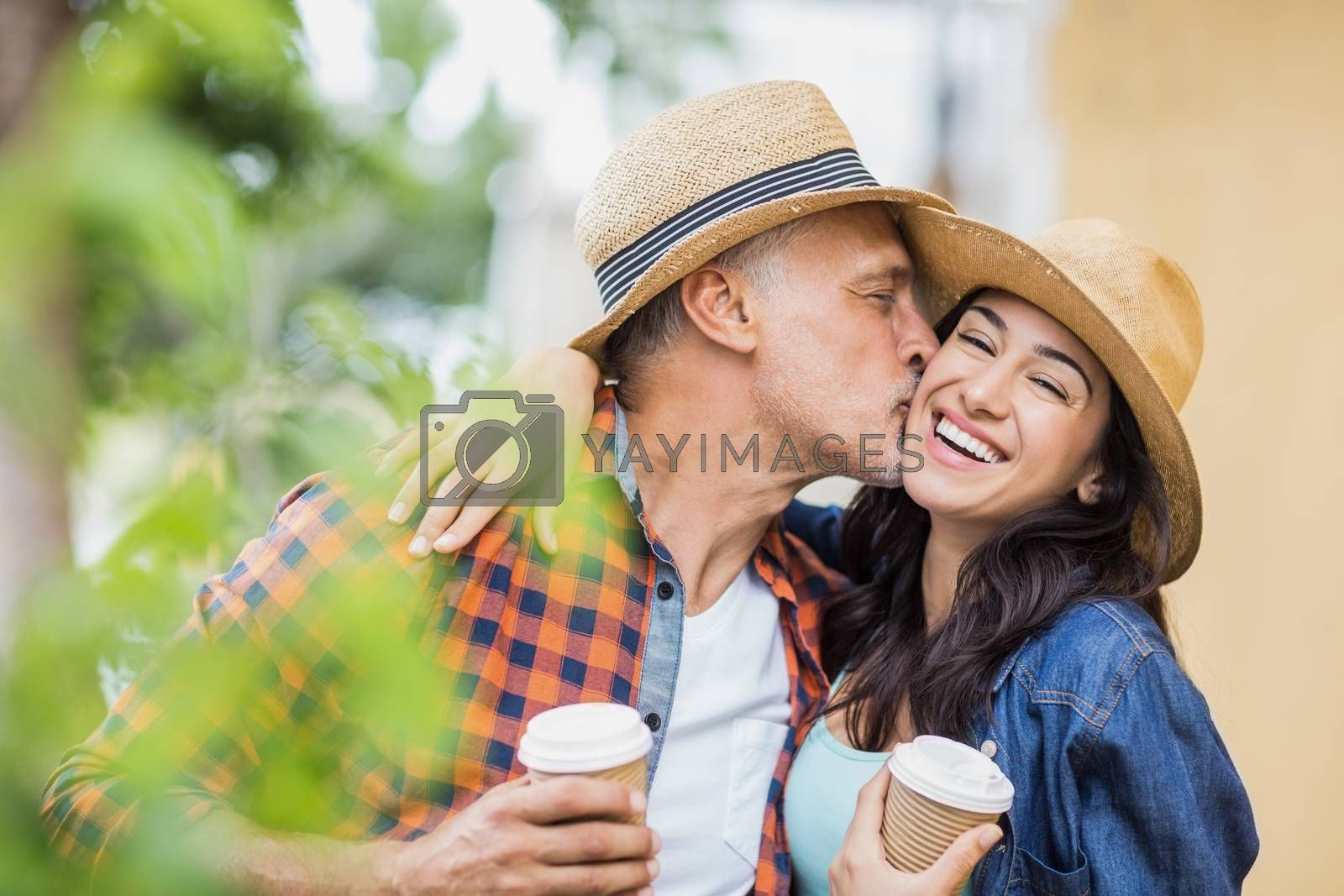 Man kissing cheerful woman with coffee cups