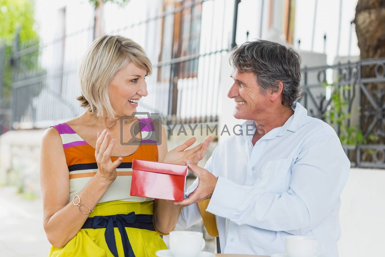 Happy man giving gift to woman while sitting at cafe