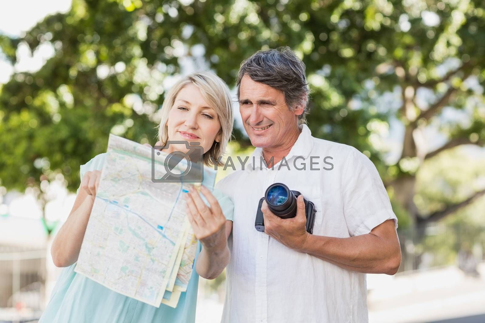 Couple looking at map with camera in city