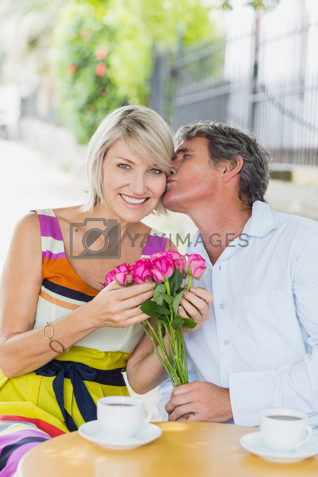 Portrait of woman being kissed by man with flowers at cafe