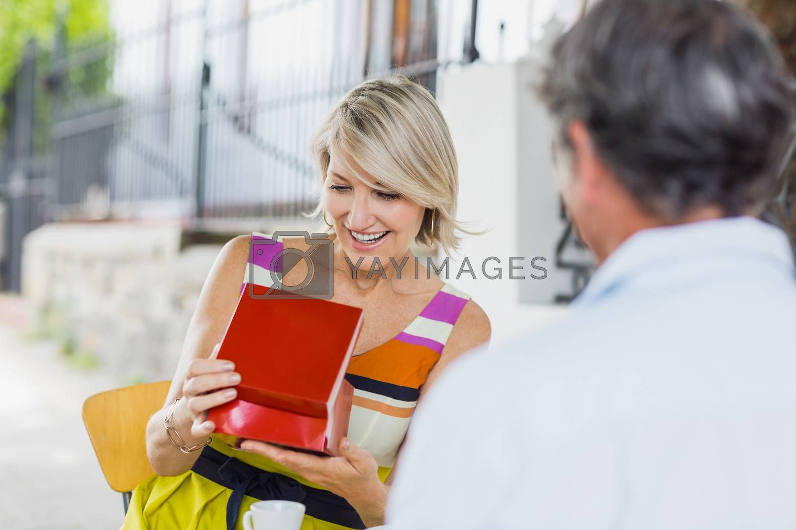 Woman looking at gift with man sitting in cafe