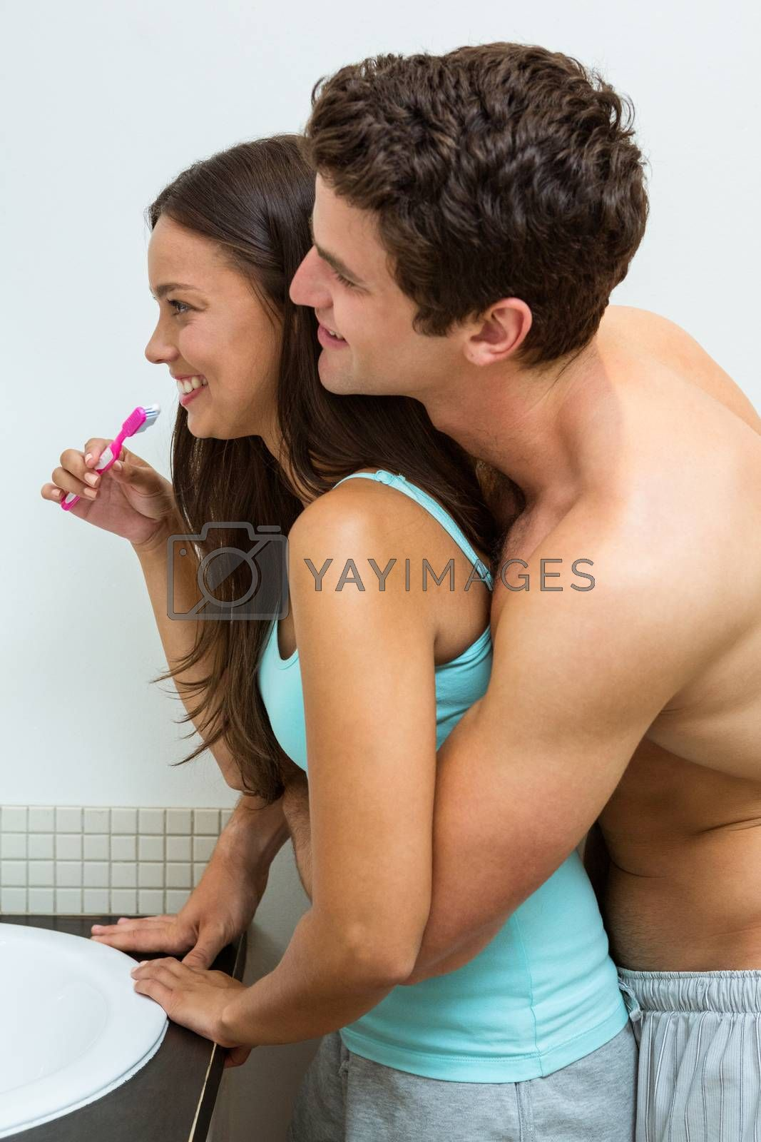 Close-up of couple hugging while brushing teeth in bathroom
