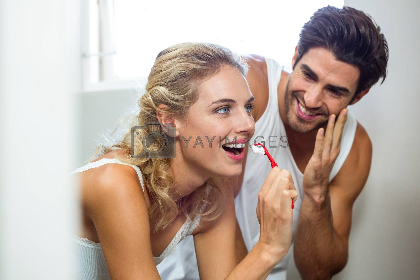 Man smiling and looking at woman while brushing teeth in bathroom