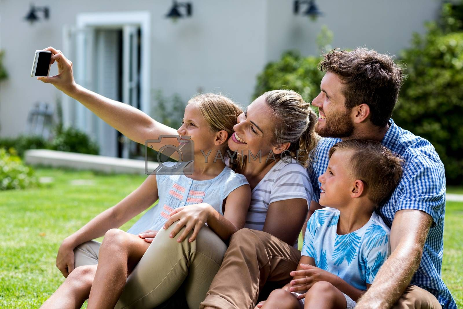 Happy mother taking selfie with family while sitting in yard