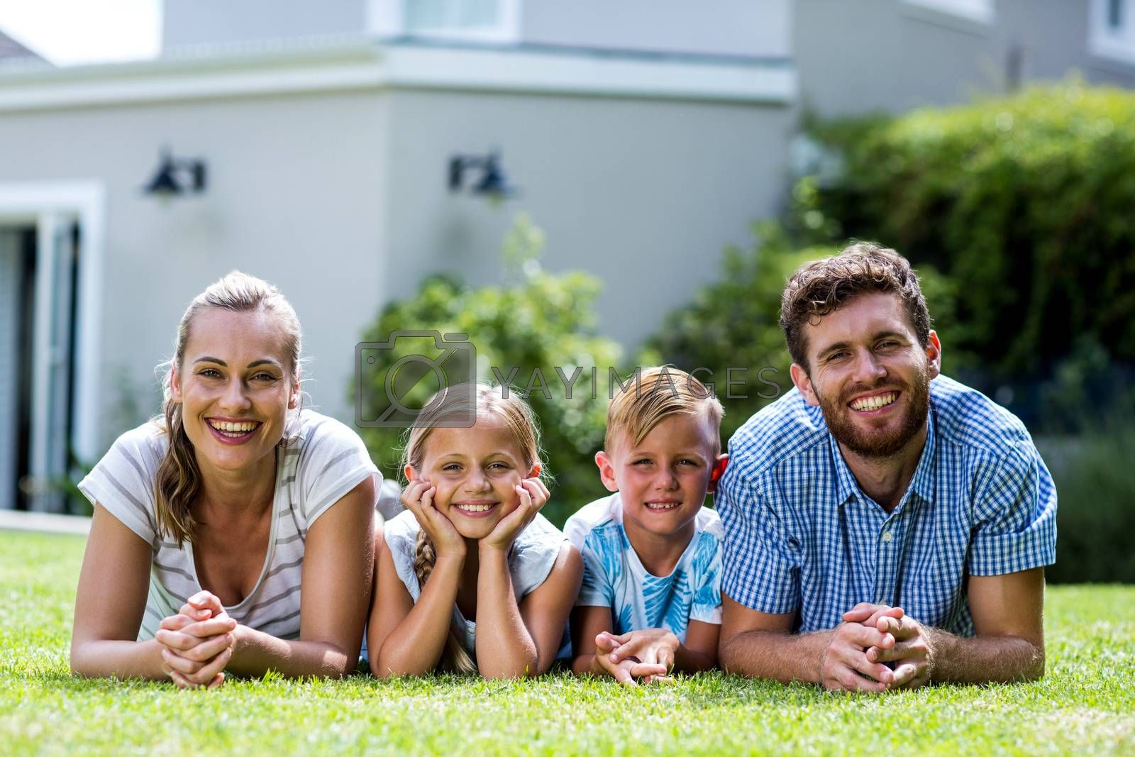 Front view of happy family lying in yard  by Wavebreakmedia
