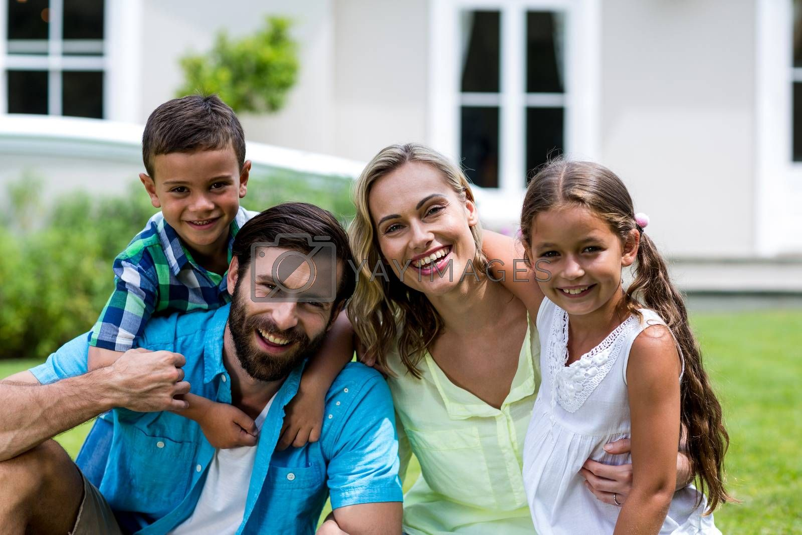 Portrait of happy family sitting on grass at yard