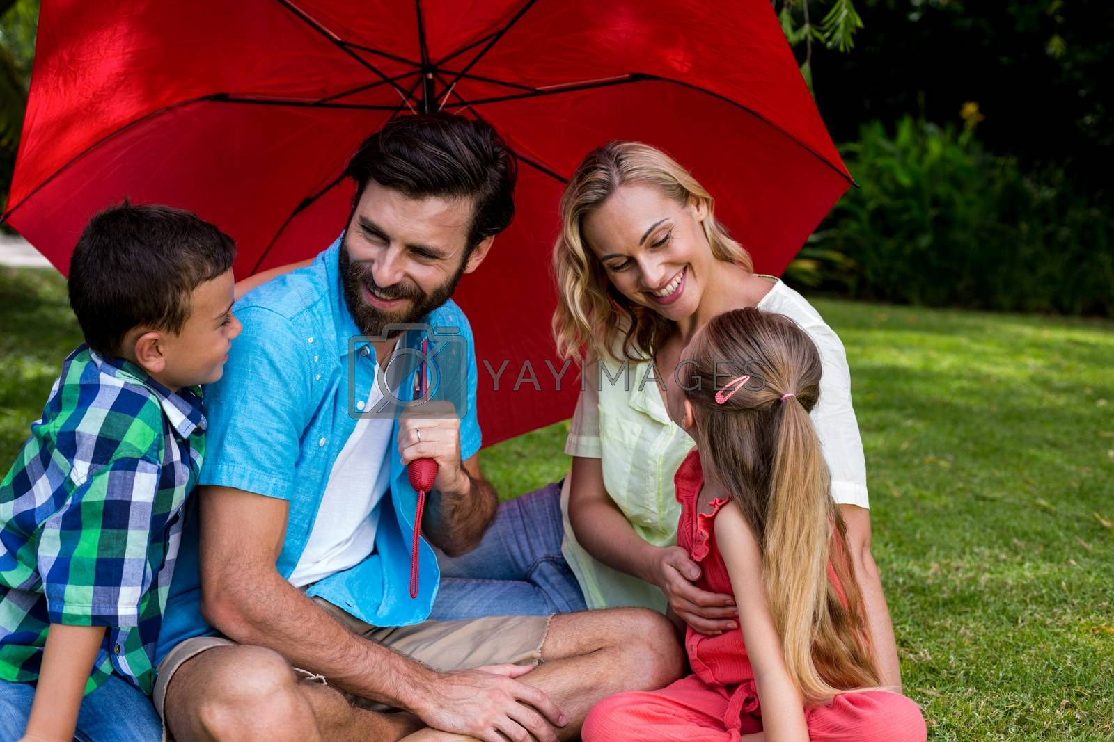 Happy family with umbrella sitting on grass at yard