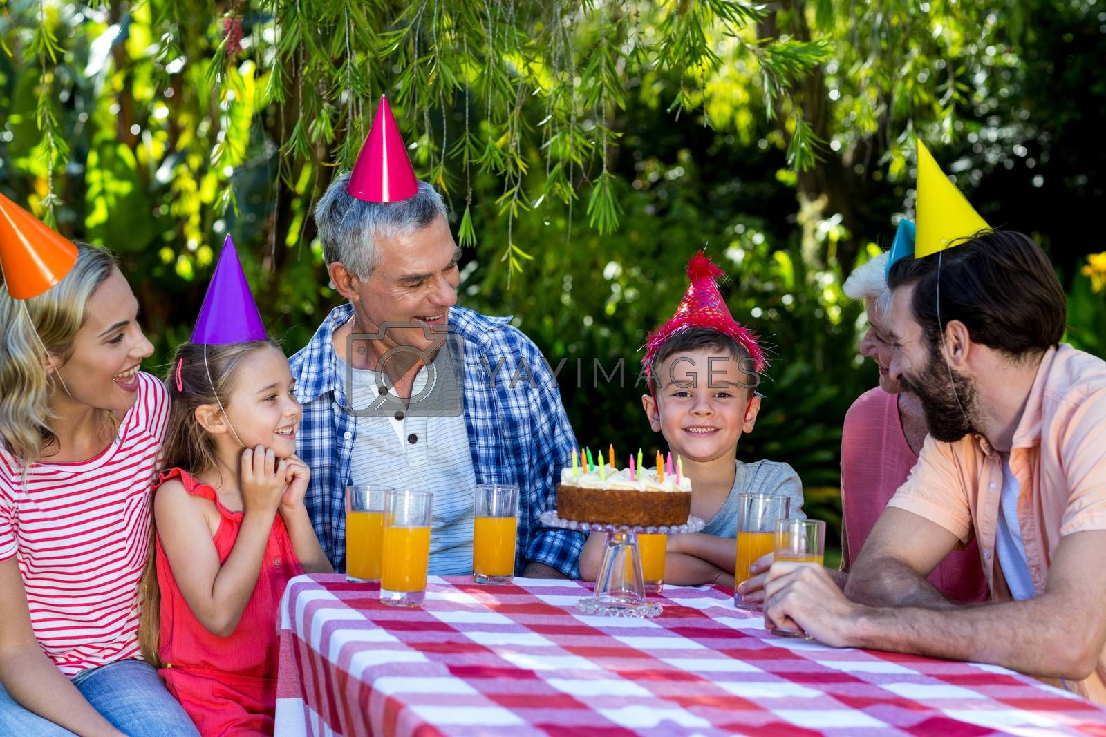 Smiling family looking at birthday boy during celebration in yard