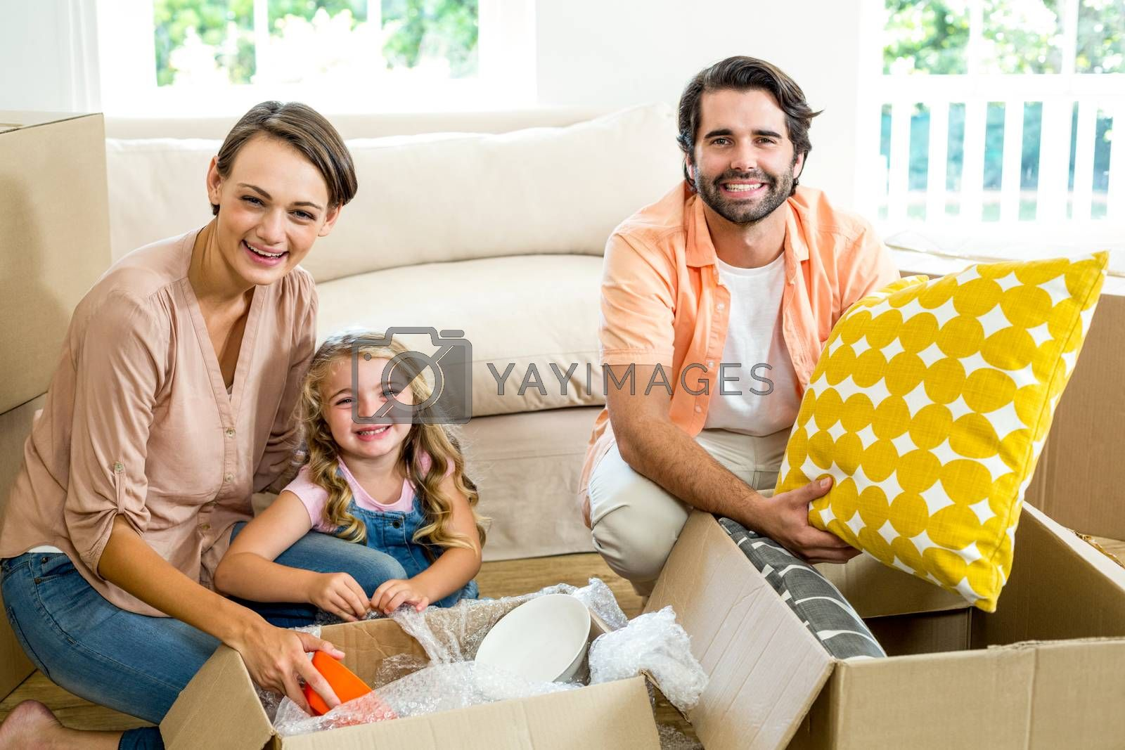 Happy family unpacking boxes in new house by Wavebreakmedia