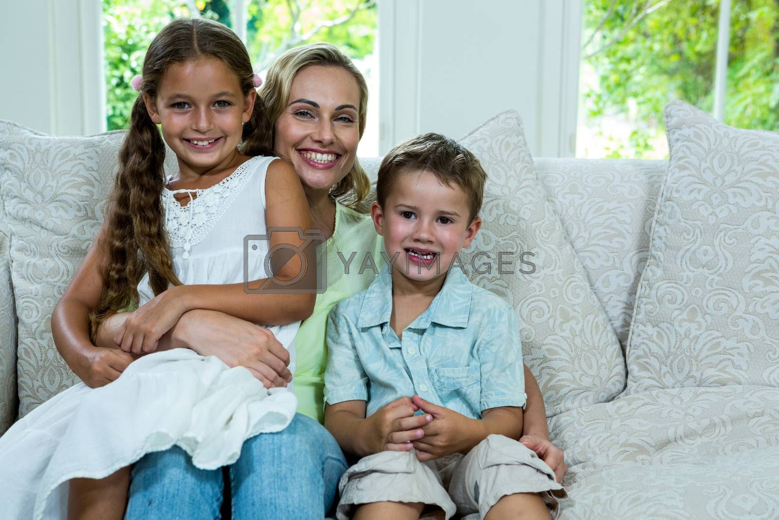 Portrait of mother with daughter and son on sofa by Wavebreakmedia