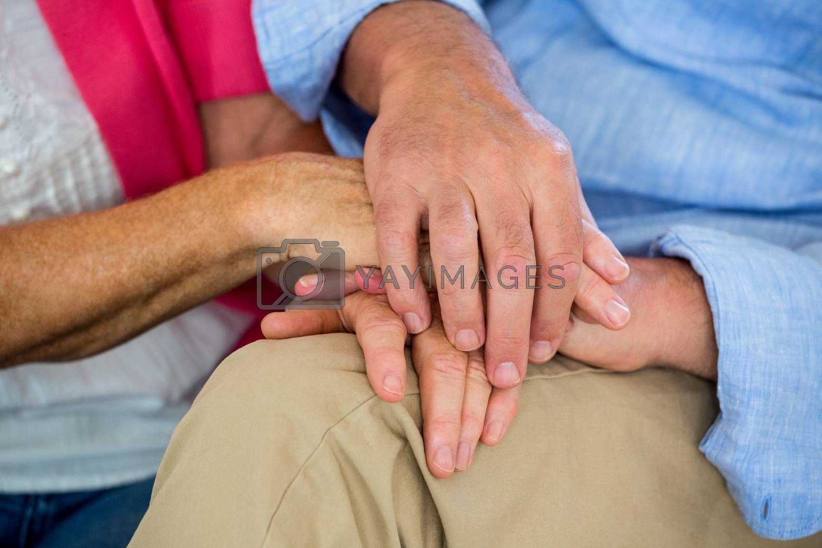 A Midsection of couple is holding hands
