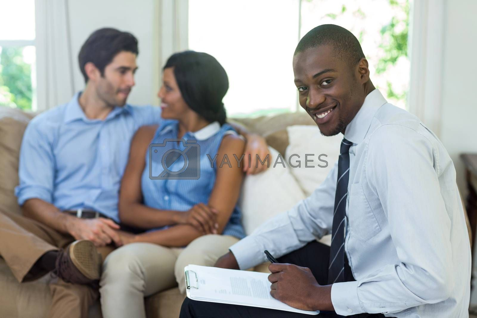 Portrait of a smiling real estate agent and couple sitting in background