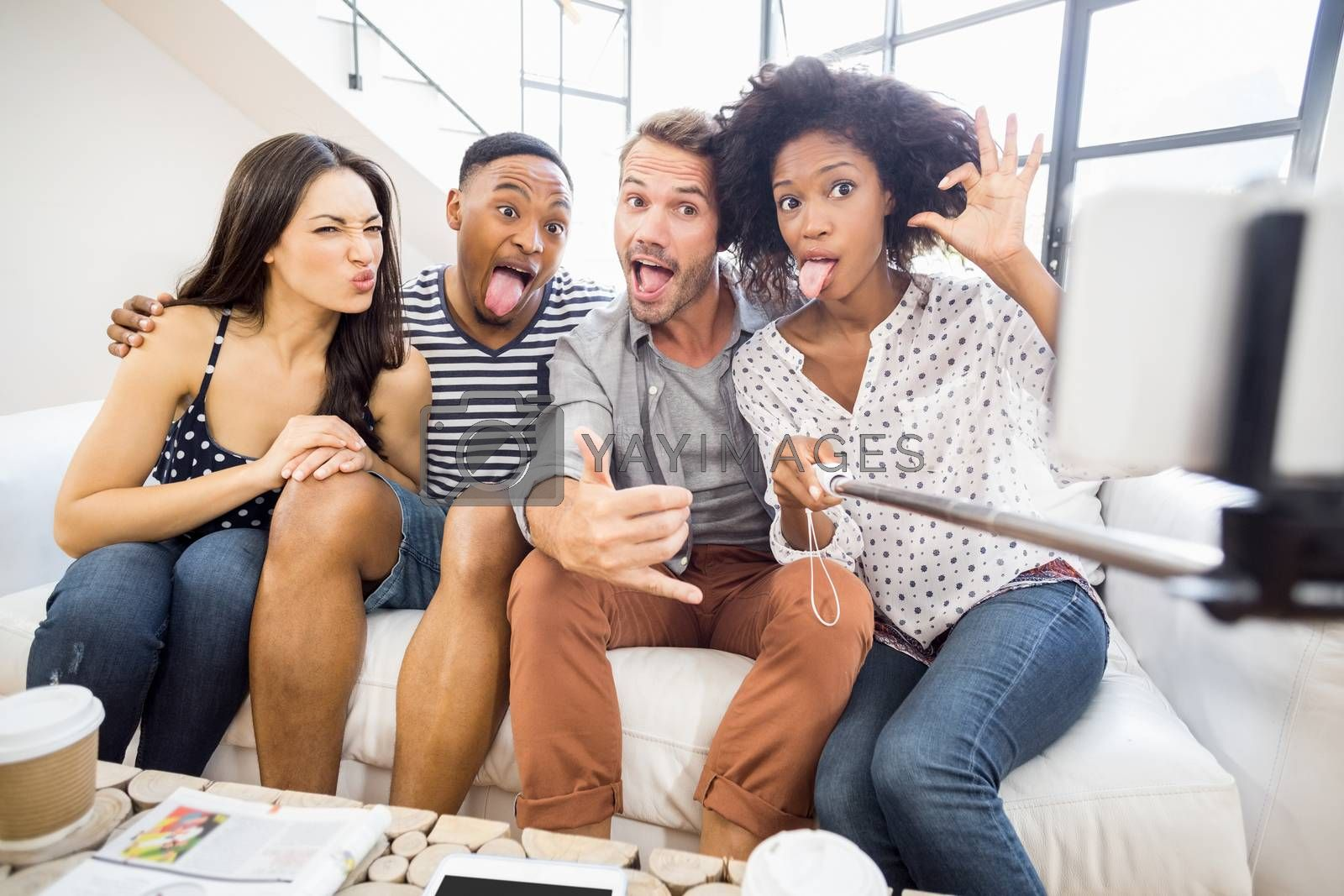 Friends making funny faces while taking a selfie in living room
