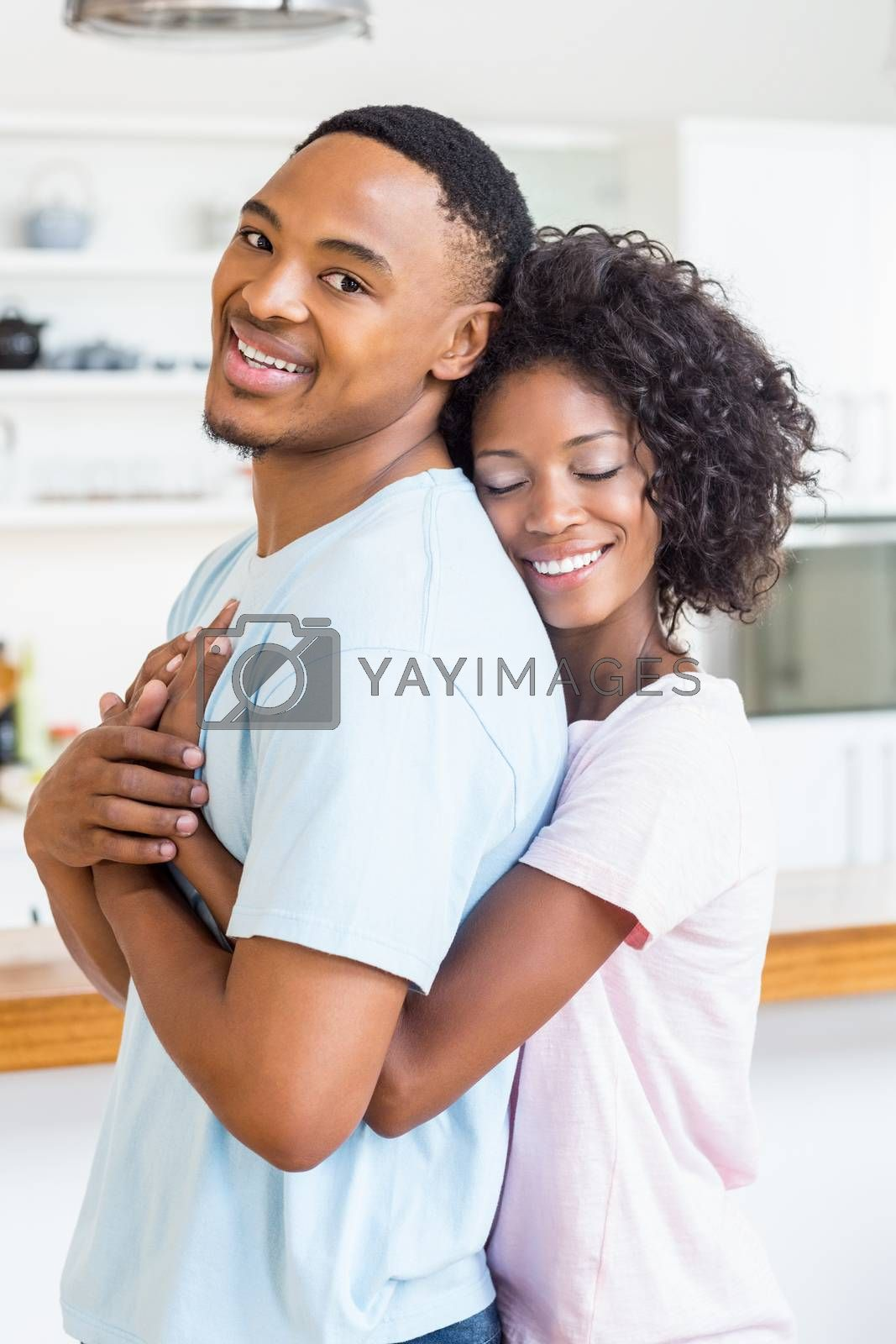 Happy young couple embracing in kitchen at home