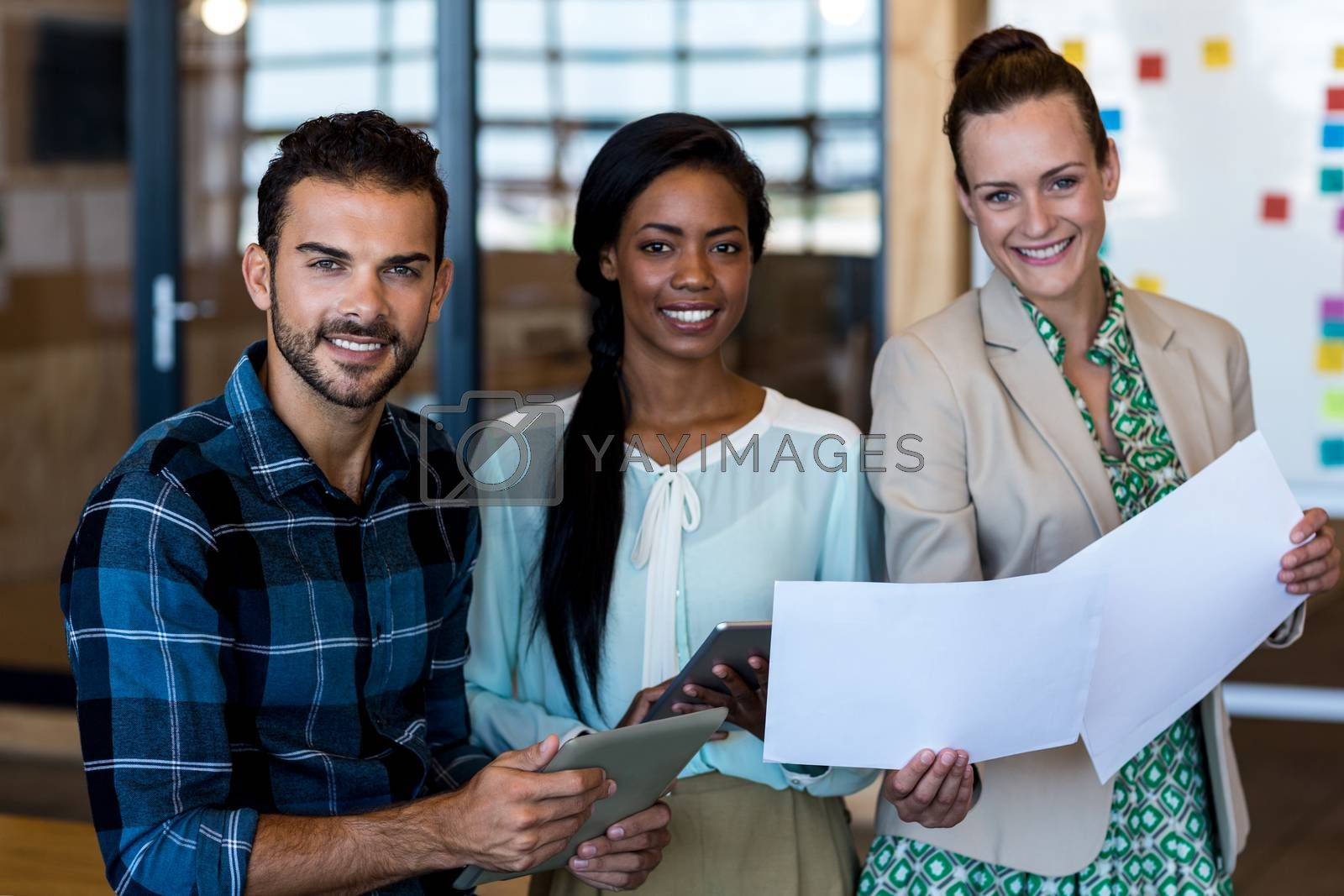 Portrait of young man and women discuss using digital tablet and document in the office