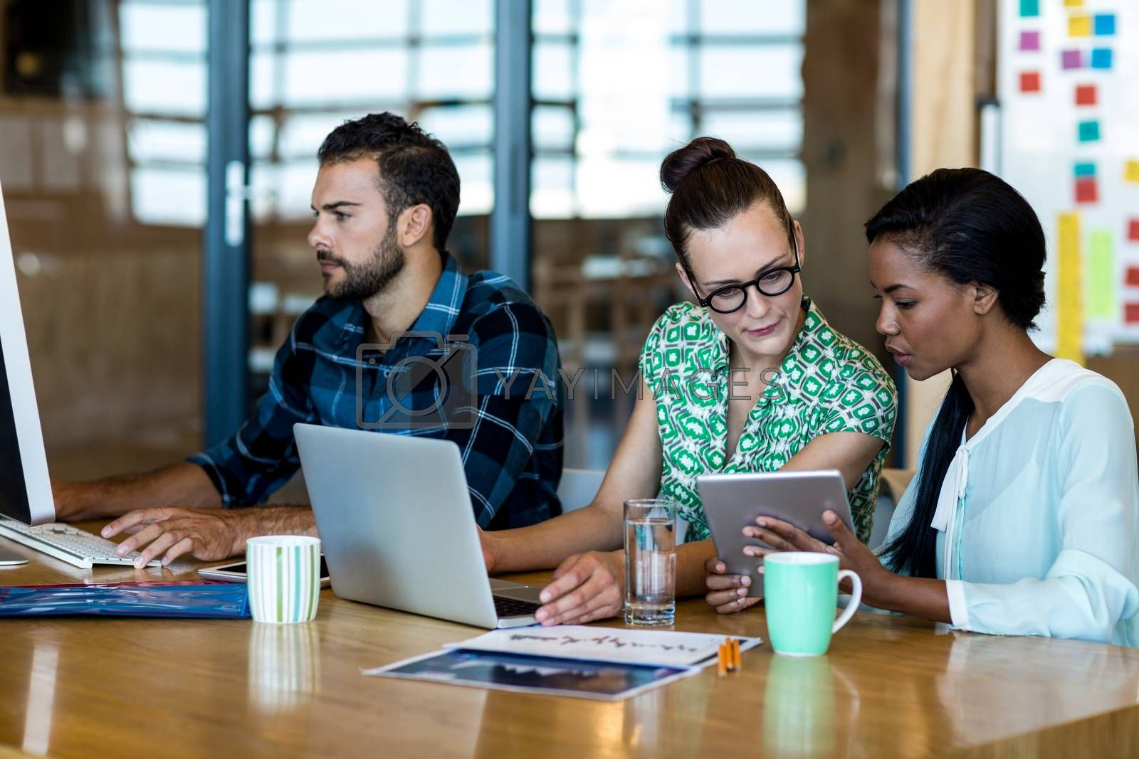 Young man and women sitting at their desk and discuss using laptop, digital tablet and personal computer in the office