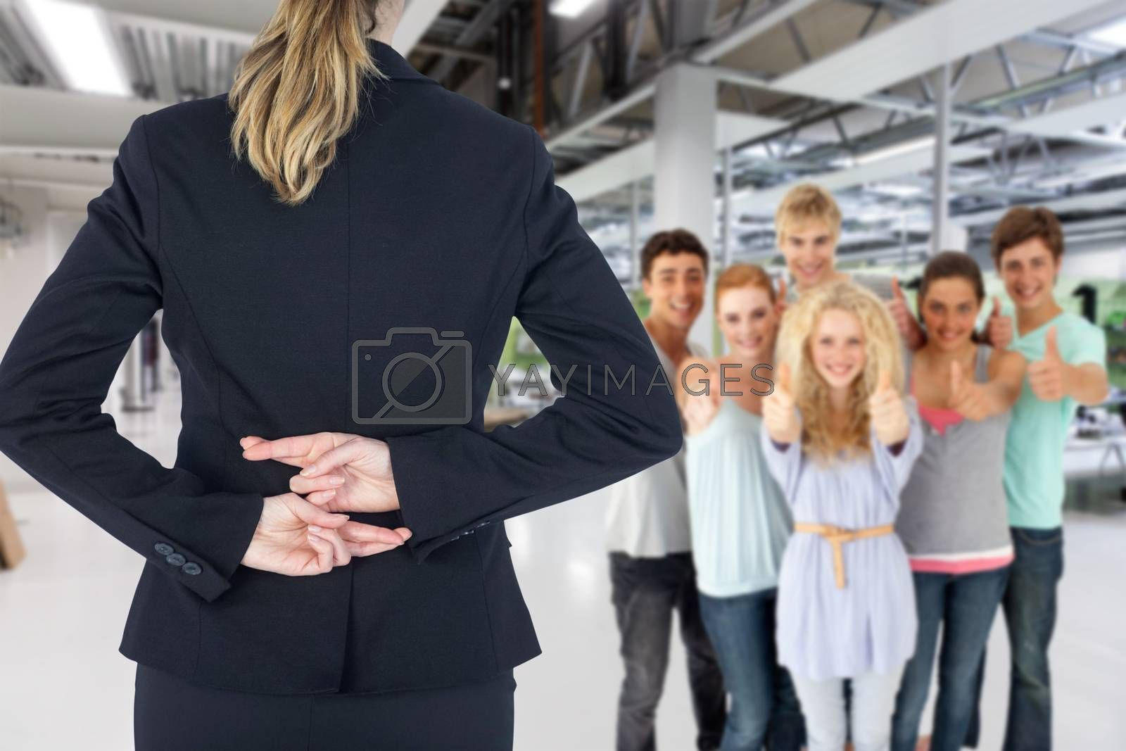Rear view of businesswoman with fingers crossed behind her back against classroom
