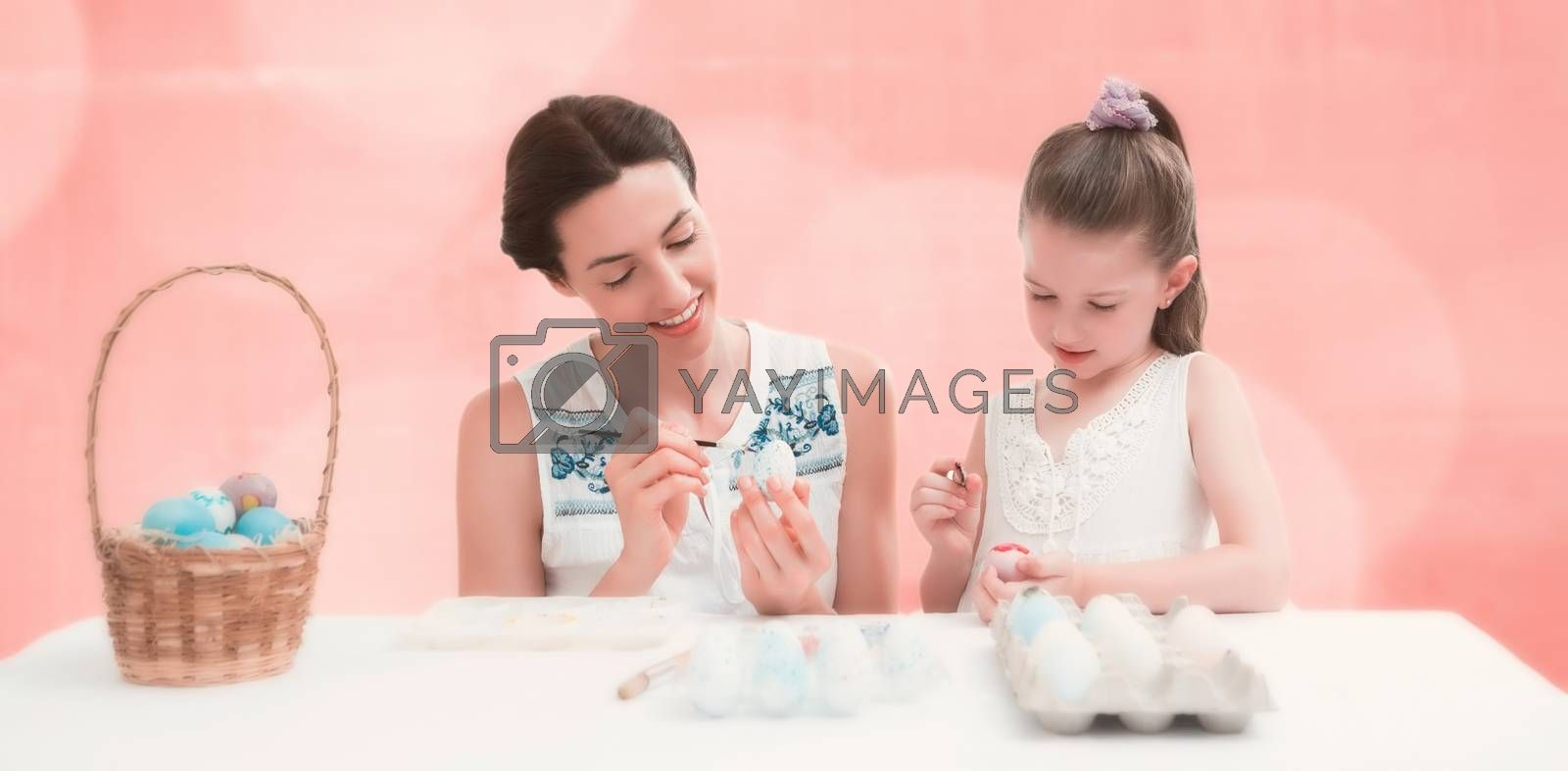 Mother and daughter painting easter eggs against background of colors