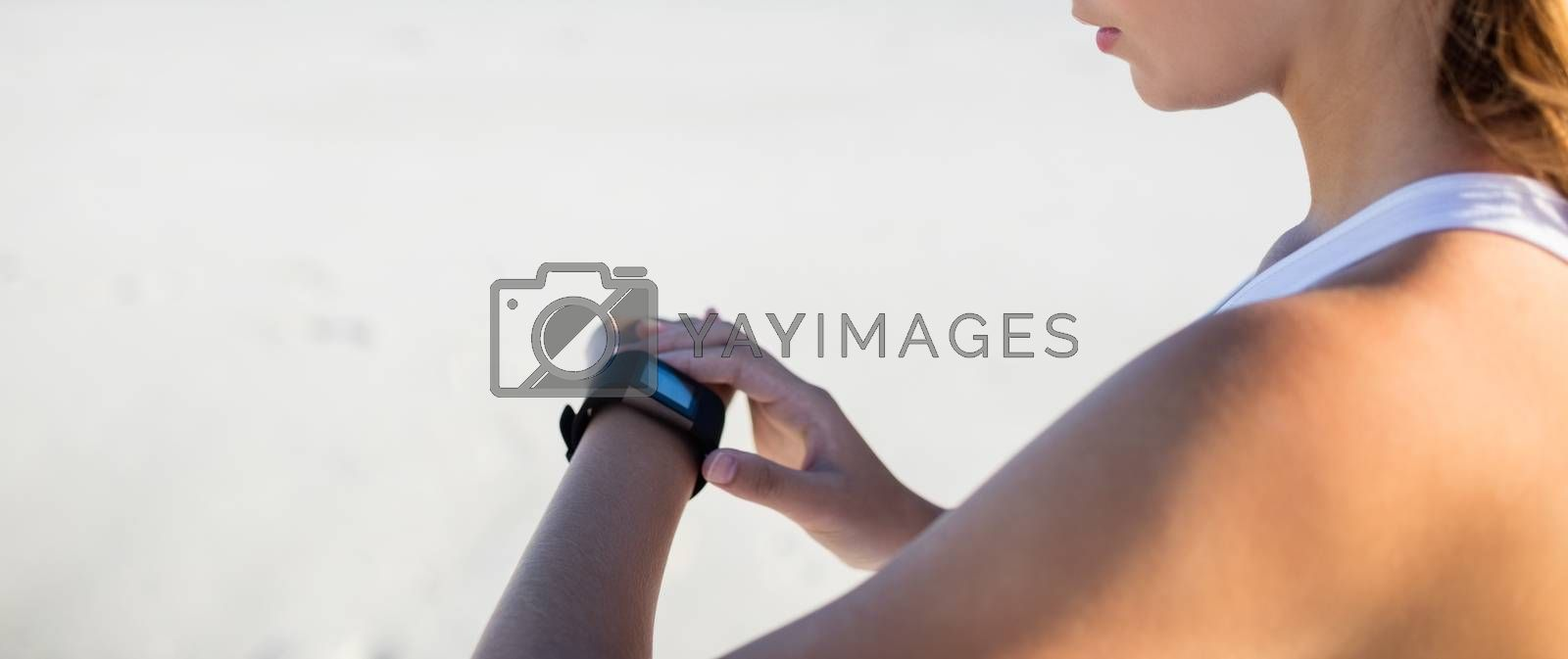 Woman using a smart watch on the beach