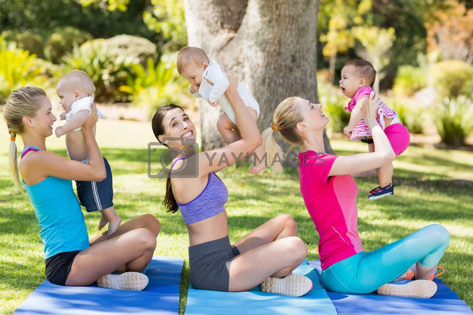Women holding their babies while exercising by Wavebreakmedia