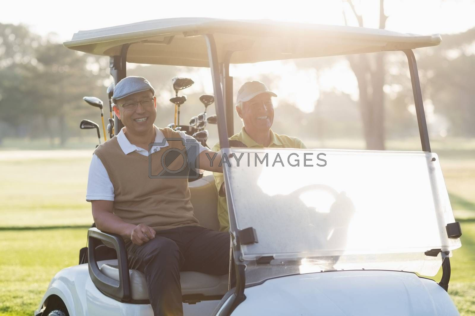 Happy golfer friends sitting in golf buggy on sunny day