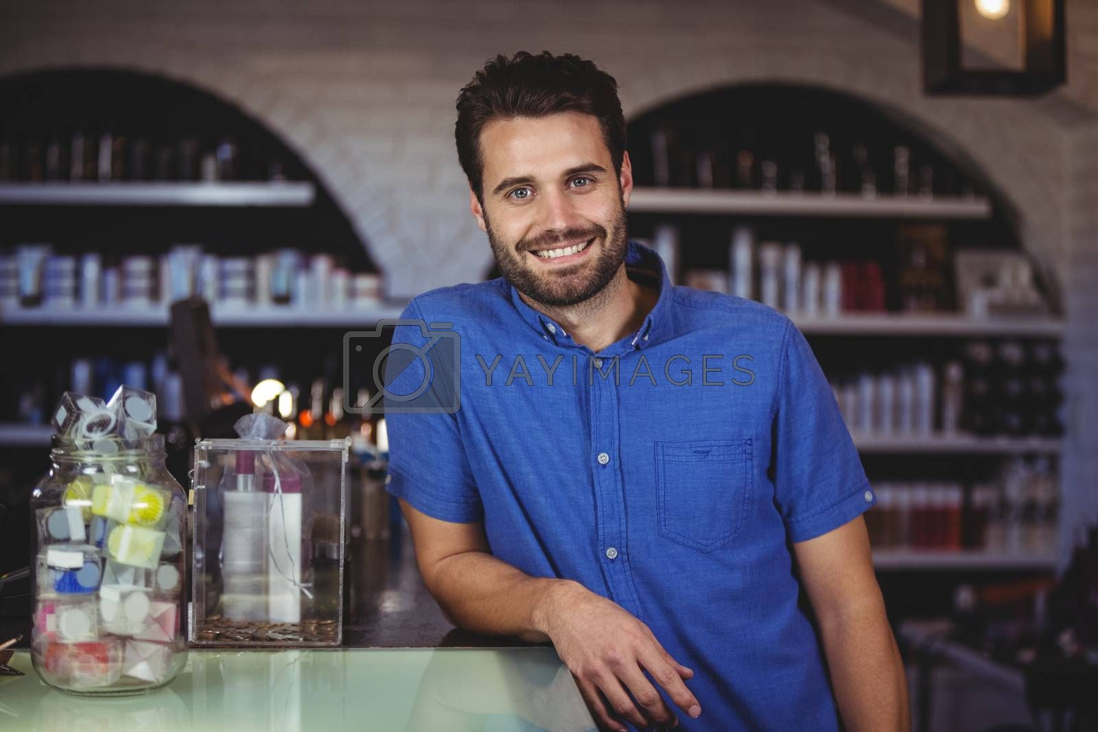 Portrait of male hairdresser leaning on table at a salon