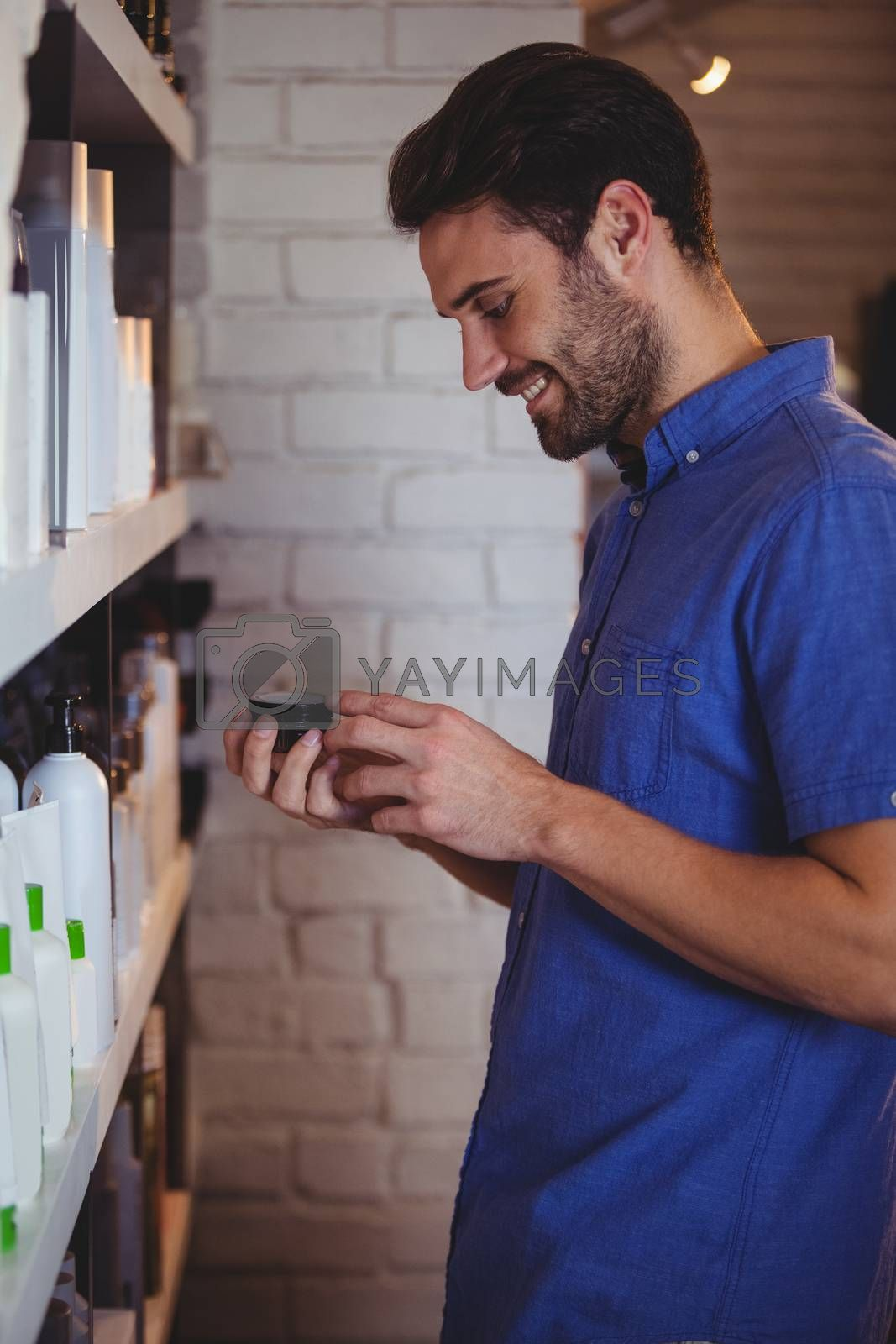 Smiling male hair dresser selecting gel from shelf at a salon