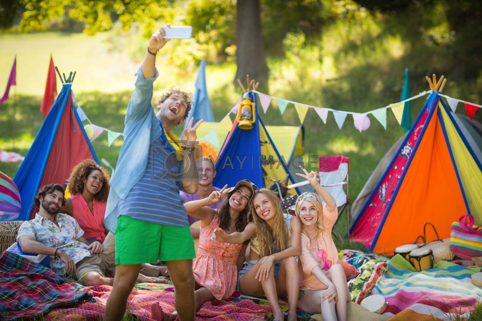 Man taking a selfie with friends at campsite on a sunny day