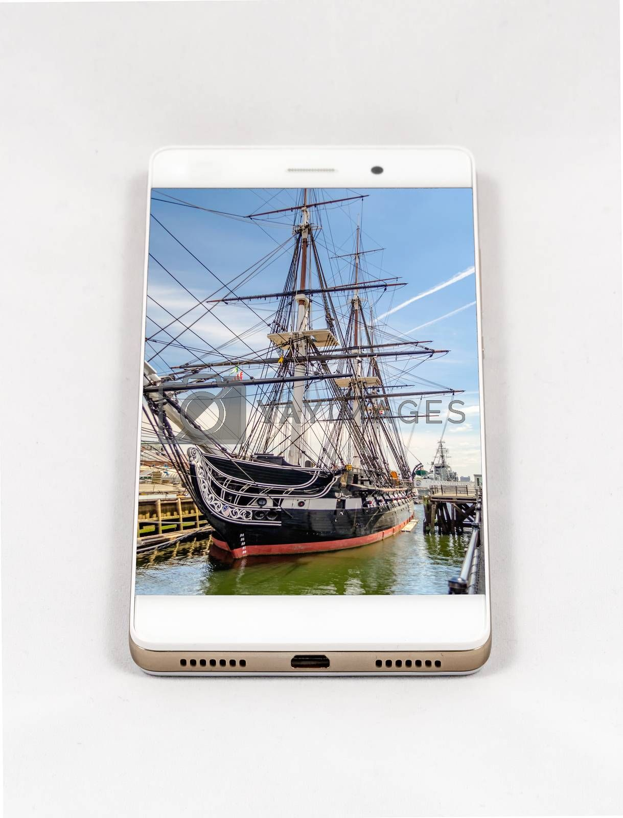 Modern smartphone with USS Constitution frigate docked in the Boston Harbor, USA. Concept for travel smartphone photography. All images in the composition are made by me and  available on my portfolio