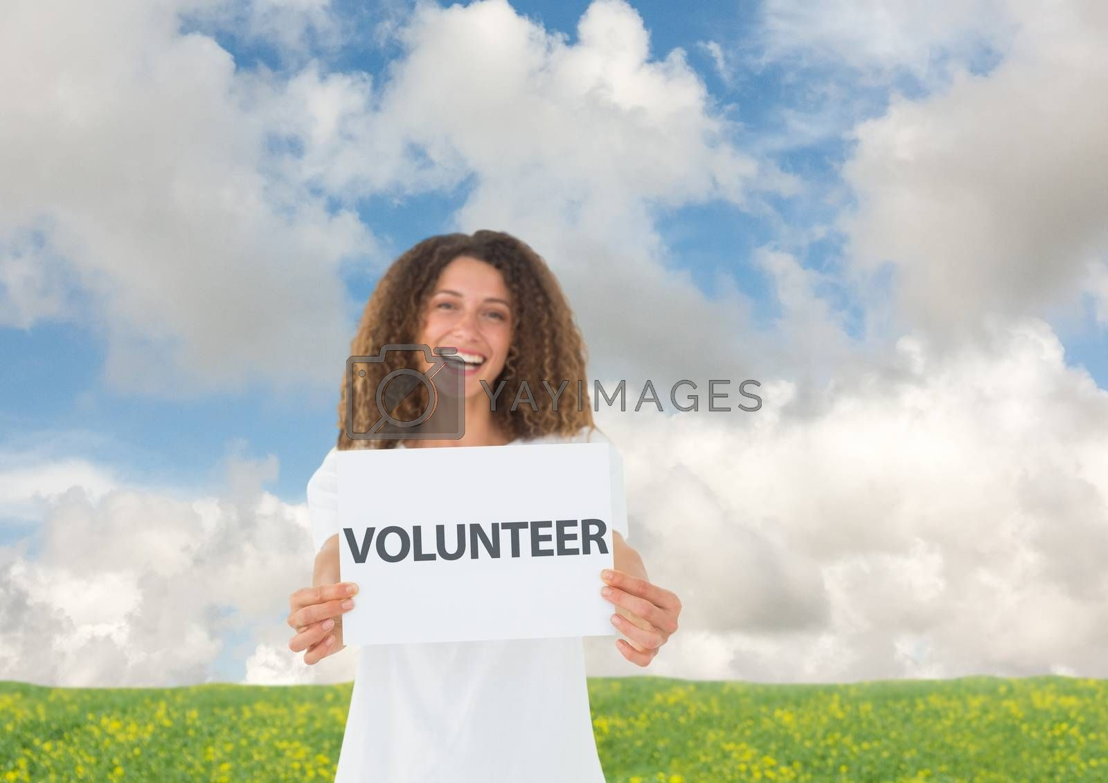Digital Composite of Smiling volunteer holding whitecard against field background