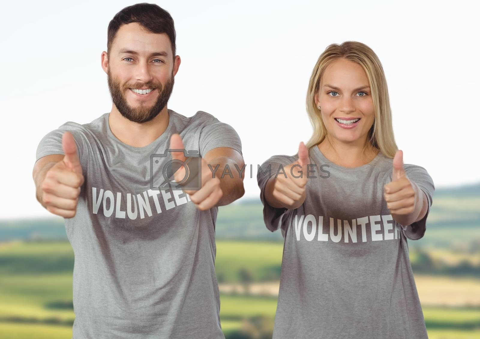 Digital Composite of Couple of volunteer thumb up against landscape background